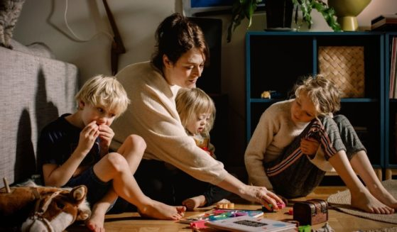 The stock photo above shows a mother playing with her children.