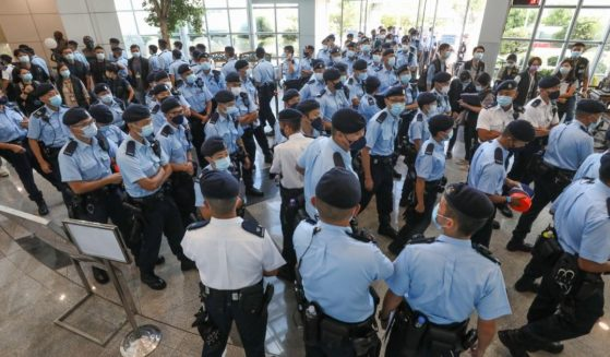 Police officers conduct a raid at the offices of the Apple Daily newspaper on Thursday in Hong Kong.