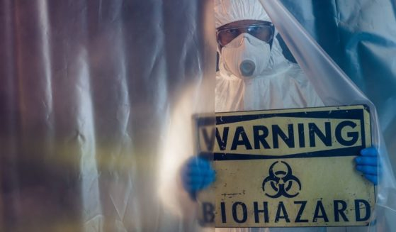 This stock photo portrays a man holding up a biohazard warning sign. One official is discussing the possibility that COVID-19 may have been part of a Chinese offensive bioweapons program.