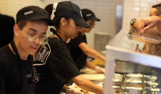 Chipotle restaurant workers fill orders for customers on April 27, 2015, in Miami.
