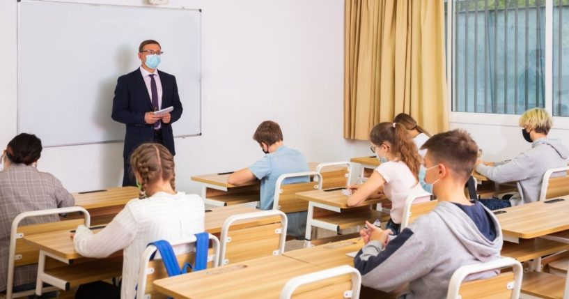 A teacher is pictured in a classroom with his students in the stock image above.