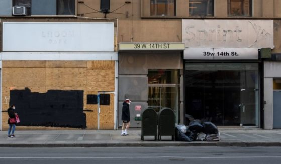 People wearing masks walk past closed retail stores on March 15, 2021, in New York City.