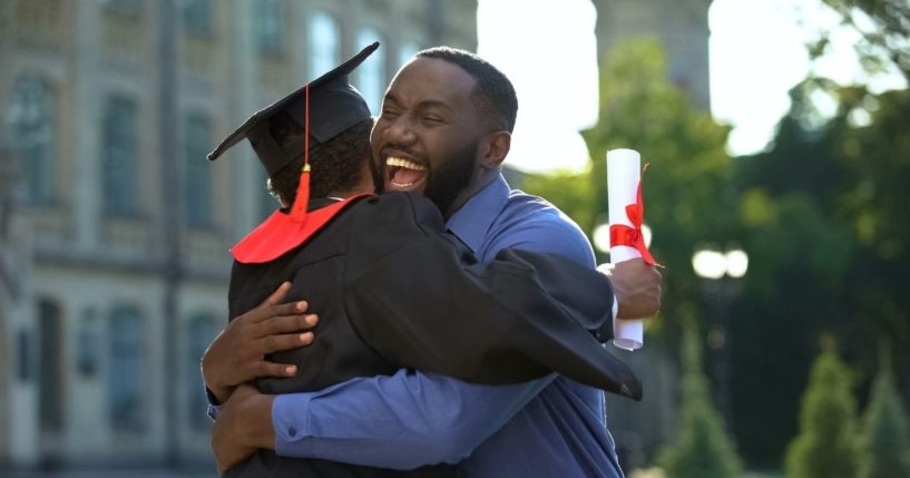 A father is pictured hugging his son after he graduates from college in the stock image above.