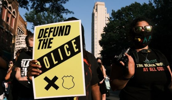 """A protester carries a sign that reads """"Defund the Police"""" during a Black Lives Matter demonstration in Richmond, Virginia, on July 3, 2020."""