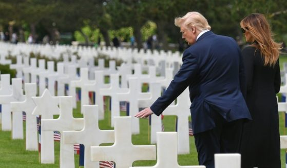 Then-President Donald Trump, left, and then-first lady Melania Trump visit graves after a French-U.S. ceremony at the Normandy American Cemetery and Memorial in Colleville-sur-Mer, Normandy, northwestern France, on June 6, 2019.