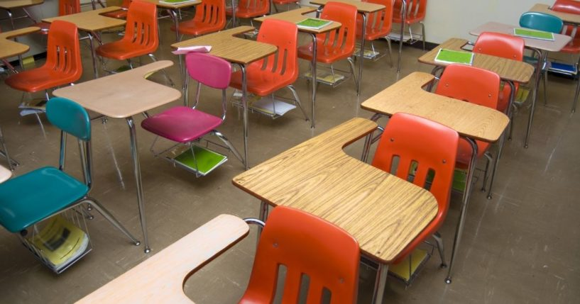 An empty school classroom is seen in the stock image above.