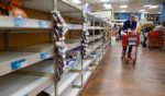 In this March 13, 2020, file photo, shoppers browse empty shelves at a supermarket in Larchmont, New York, amid panic-buying due to the coronavirus outbreak.