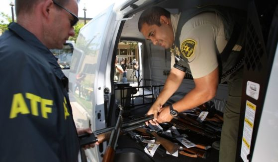 Officers begin to load confiscated weapons into a van on May 21, 2009, in the Los Angeles-area community of Lakewood, California.
