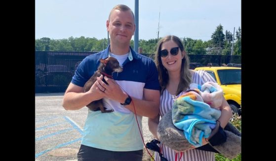 Officer James Crosser with his wife, Olivia, and Fern, an elderly chihuahua he found tied to a mile marker and ended up adopting.