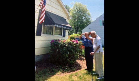 Jack Henrique of Hampden County, Massachusetts, salutes the flag alongside his 100-year-old neighbor, Mario Arcobello.