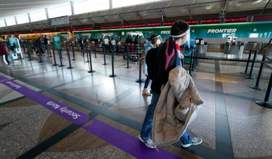 Travelers walk past the Frontier Airlines ticketing counter in the main terminal of Denver International Airport on Dec. 31.