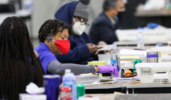 Workers scan ballots and check for discrepancies at the Georgia World Congress Center in Atlanta on Jan. 5, 2021, during the Georgia Senate runoff elections.