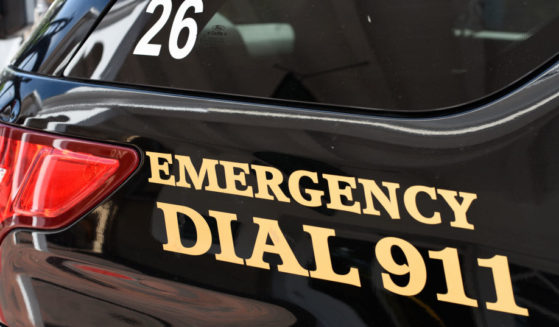 A police car with 'Emergency Dial 911' on its side in Santa Fe, New Mexico.