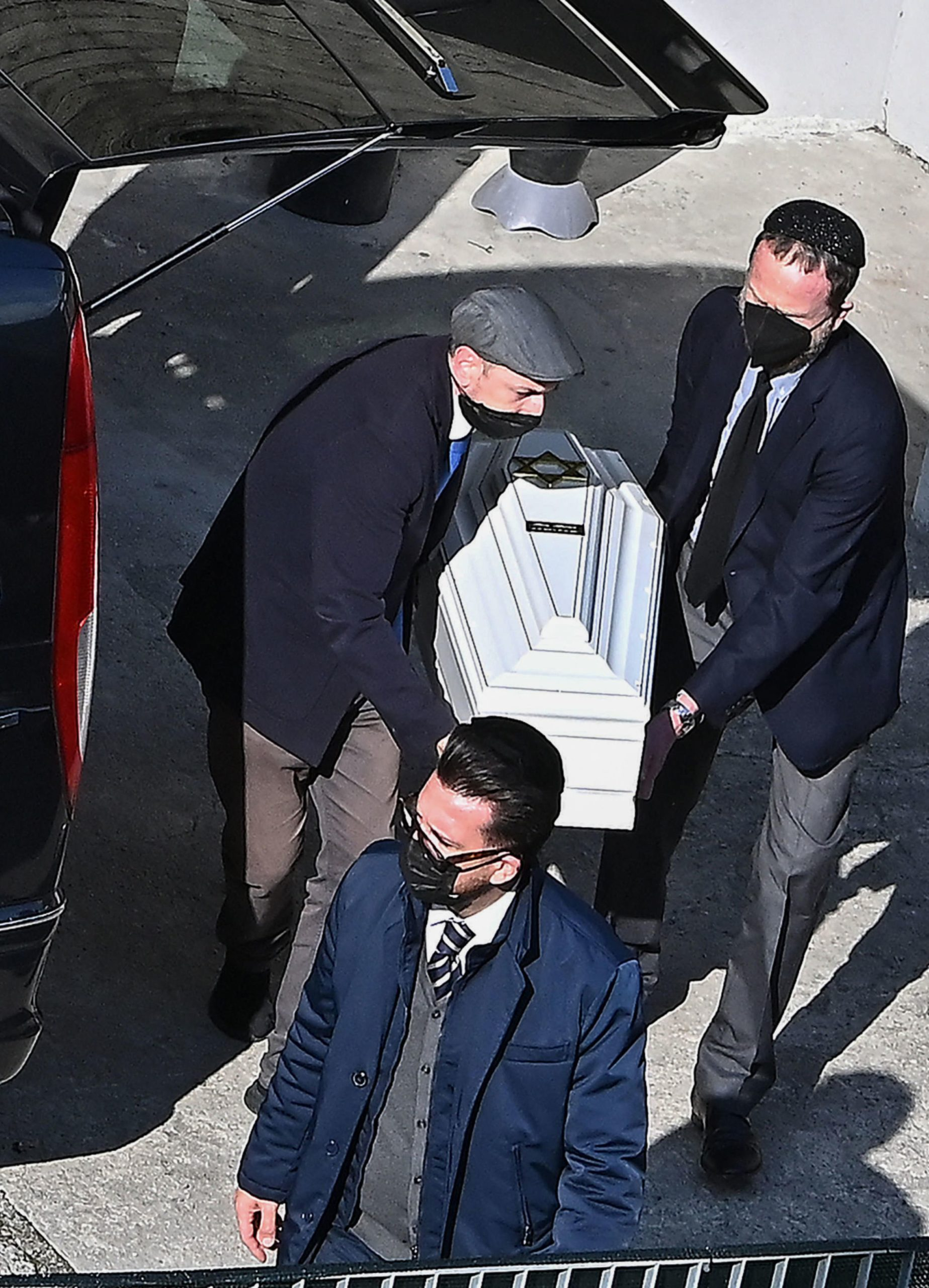 A photo obtained from Italian news agency Ansa and taken on May 26, 2021 outside the morgue of the Castelli hospital of Verbania-Pallanza on Lake Maggiore, shows people carrying the coffin of one of the Israeli victims of the cable car crash that occured in nearby Stresa on May 23.
