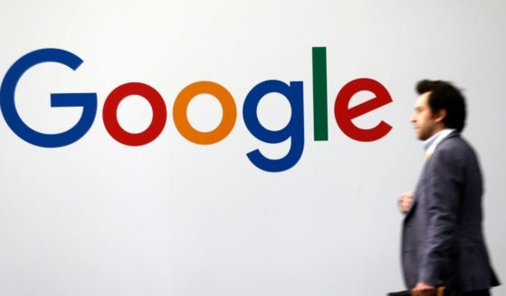 A man passes by the logo of Google on May 16, 2019, in Paris.