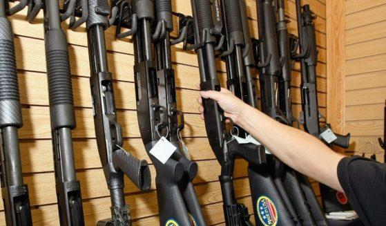 A sales associate takes a gun from a display of shotguns at The Gun Store on Nov. 14, 2008, in Las Vegas.