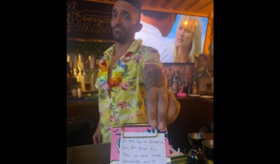 Bartender Max Gutierrez hands a disguised note to a patron being harassed by a male customer at a bar in St. Petersburg, Florida.