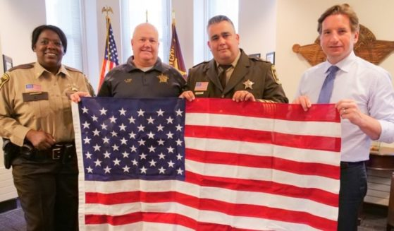 Democratic Rep. Dean Phillips of Minnesota, far right, delivers an American flag to Hennepin County Sheriff Dave Hutchinson, center right, on June 2, 2021.