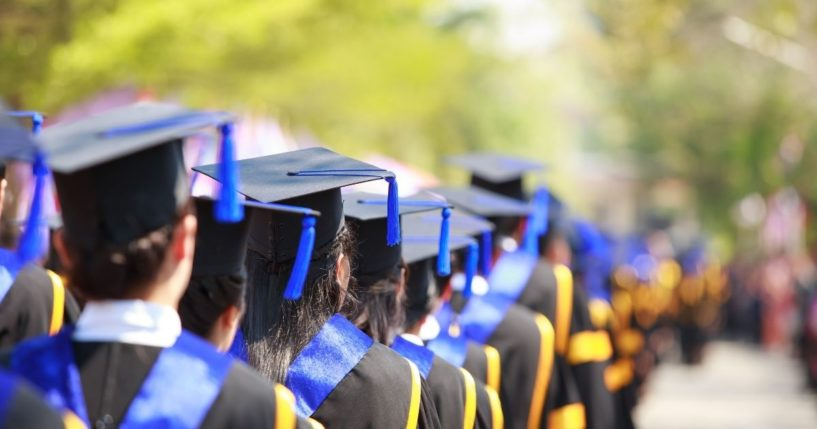 Students are pictured at a high school graduation in the stock image above.