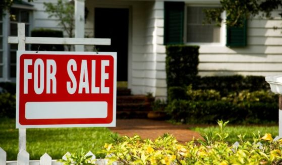 """A """"for sale"""" sign is pictured in front of a house."""