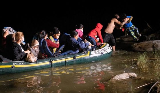A smuggler lifts an immigrant child on to the bank of the Rio Grande after illegally crossing the U.S.-Mexico border near Roma, Texas, early on April 30.