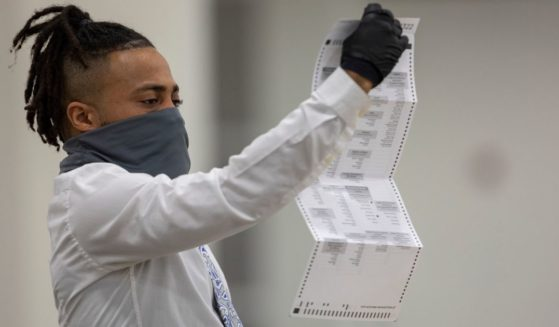 A worker with the Detroit Department of Elections inspects an absentee ballot at the Central Counting Board in the TCF Center on Nov. 4, 2020, in Detroit.