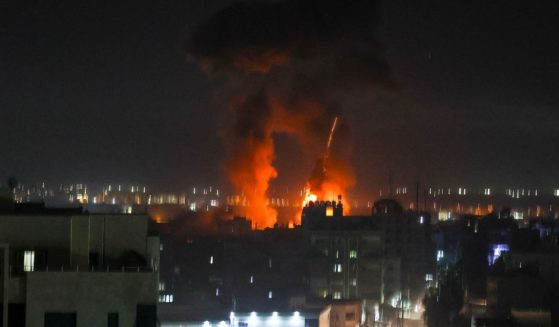 Explosions light up the night sky above buildings in Gaza City on Friday.