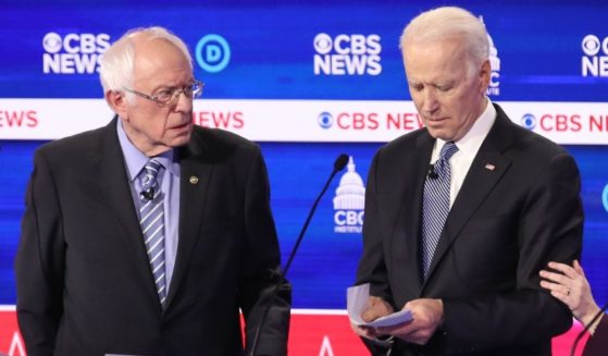 Then-presidential candidates independent Sen. Bernie Sanders of Vermont, left, and now-President Joe Biden interact at a break during the Democratic presidential primary debate at the Charleston Gaillard Center on Feb. 25, 2020, in Charleston, South Carolina.