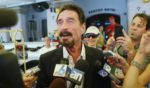 John McAfee talks to the media in 2012 in the photo above.