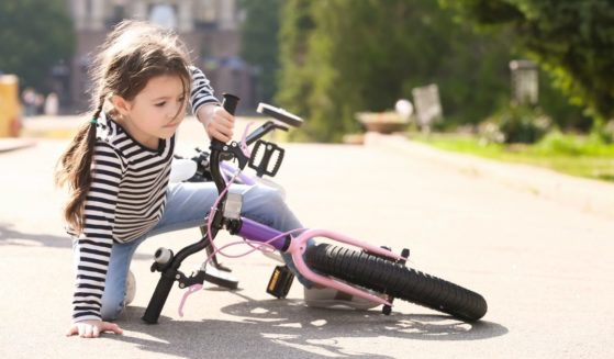 A child is pictured after falling off her bike in the stock image above.
