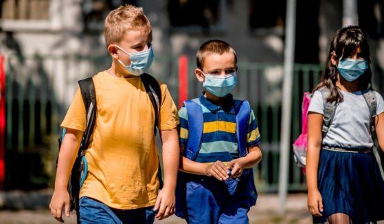 Children wear masks as they go to school.