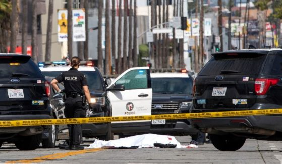 An LAPD police officer stands at the corner of Fairfax Avenue and Sunset Boulevard where a body covered in a white sheet lies on the pavement in Los Angeles on April 24, 2021.