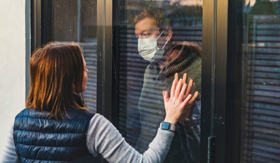 This stock photo portrays a woman looking in at a man wearing a mask in quarantine. A recent MedRxiv study found that mask mandates did not have a significant impact on lowering the spread of the coronavirus.