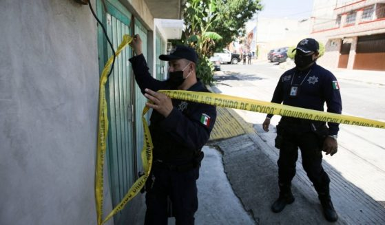 A police officer marks a security perimeter around the house where bones were found under the floor in the Atizapan municipality of the State of Mexico on May 20, 2021.