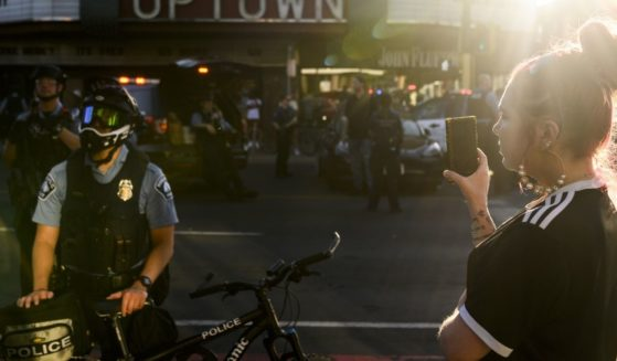 A woman appears to record police officers with her phone as they clear an intersection where protesters were staging an anti-police demonstration on June 4 in Minneapolis.