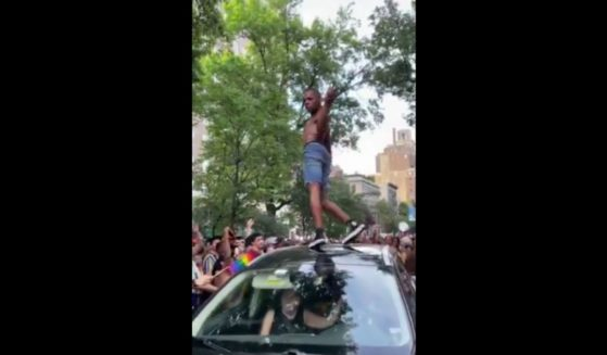 In a video shared on Twitter on Monday, a Pride March celebrator jumps on a moving vehicle and dances provocatively on it
