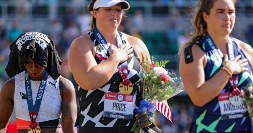Third-place finisher Gwen Berry turns away from the U.S. flag with a T-shirt over her head as the national anthem is played while DeAnna Price, center, first place, and Brooke Andersen, second place, stand respectfully on the podium after the women's hammer throw final of the Olympic track and field team trials at Hayward Field in Eugene, Oregon, on Saturday.