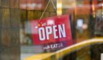 """A """"We Are Open"""" sign is seen outside a restaurant in Kips Bay on April 27, 2020, in New York City."""