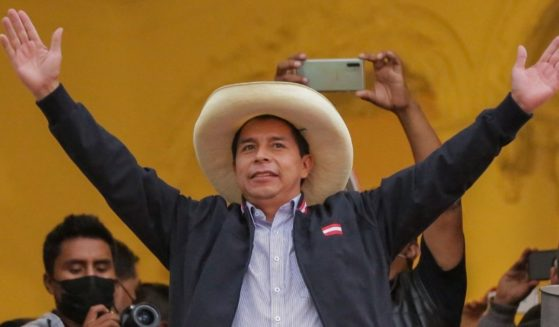 Peruvian presidential candidate Pedro Castillo gestures at supporters from a balcony of his party's headquarters in Lima on June 7.