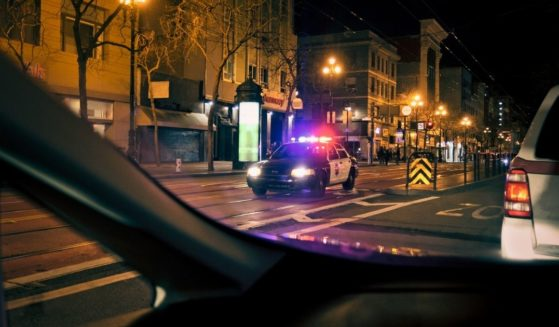 A police car drives with its lights on down a street at night