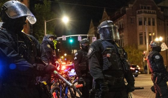Portland police stand guard as tensions rise with a small group of protesters on April 20, 2021 in Portland, Oregon.