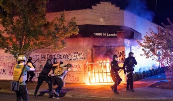 Police officers in Portland, Oregon, disperse a crowd after rioters set fire to the Portland Police Association building early in the morning of Aug. 29, 2020.