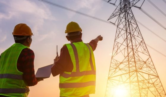 The above stock photo shows two workers inspecting the electricity high-voltage pole.