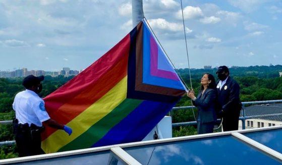 "Interior Secretary Deb Haaland raises the ""Progress Pride"" flag above her department's headquarters in Washington, D.C."