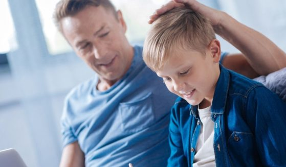 A proud father is seen patting his son on the head in the stock image above.