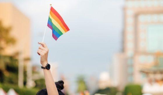A hand holds a rainbow flag.