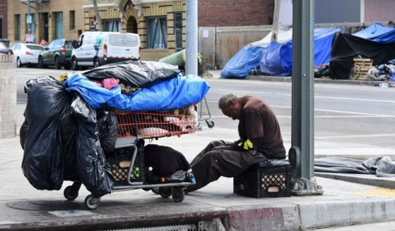 A homeless man sits beside his belongings on the streets in the Skid Row community of Los Angeles on April 26, 2021.