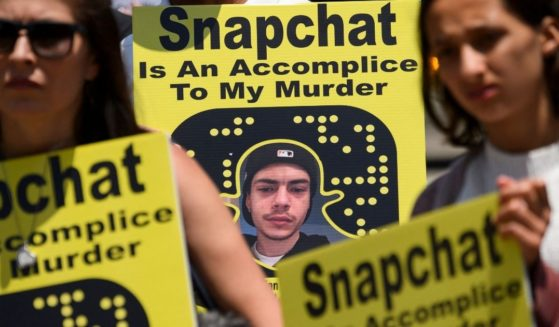 Family and friends of people who died after being poisoned by pills containing fentanyl carry signs as they protest near the Snap, Inc. headquarters, makers of the Snapchat social media application, on June 4 in Santa Monica, California.