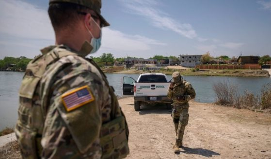 Border Patrol agents are pictured standing in front of the Rio Grande and a suburb of the Mexican city of Ciudad Miguel Aleman in the southern Texas border city of Roma.