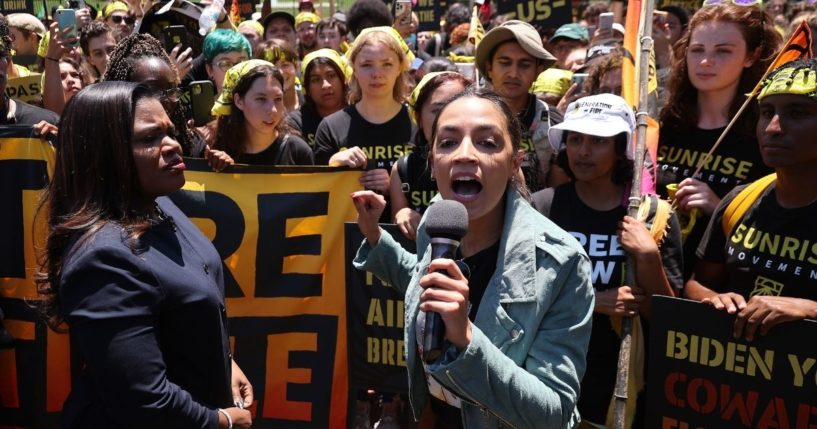 Democratic Rep. Cori Bush of Missouri, left, and Democratic Rep. Alexandria Ocasio-Cortez of New York rally hundreds of young climate activists in Lafayette Square on the north side of the White House to demand that President Joe Biden work to make the Green New Deal into law on Monday in Washington, D.C.